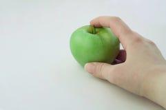 Grönt äpple i handen Arkivfoto
