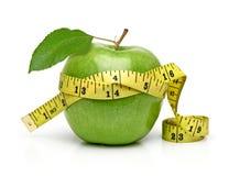 Grönt äpple med att mäta bandet Arkivfoto