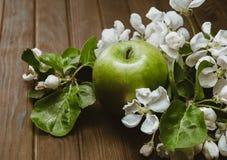 Grönt äpple med blomningar på trätabellen Arkivfoto