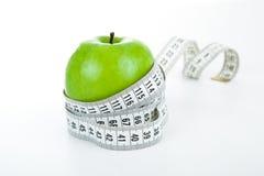 Grönt äpple med en linjal royaltyfri bild