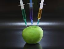 Grönt äpple med injektionssprutor arkivbilder