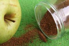 Grönt äpple med kanel i krus Arkivbild