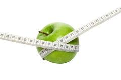 Grönt äpple med mätningsbandet Arkivbilder