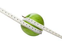 Grönt äpple med mätningsbandet Royaltyfri Fotografi