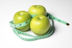 Grönt äpple med mått längden på vit bakgrund Arkivfoton