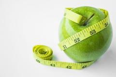Grönt äpple med midjan och mätabandet Royaltyfria Foton