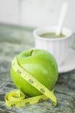 Grönt äpple med midjan och mätabandet och kaffe Arkivbild