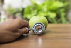 Grönt äpple med stetoskopet för vård- begrepp Arkivbild