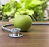 Grönt äpple med stetoskopet för vård- begrepp Arkivfoton