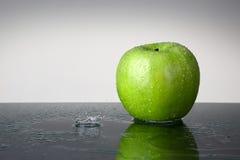 Grönt äpple med vattendroppe Arkivfoto