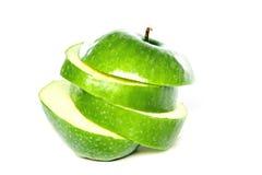grönt äpple och äppleskivor på en vit bakgrund Arkivbilder