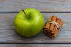 Grönt äpple och hög av kanelbruna pinnar Arkivbilder