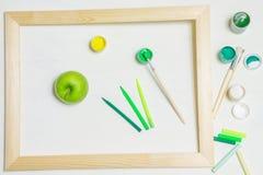 Grönt äpple och målarpenslar i en träram arkivfoton