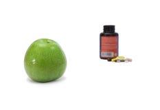 Grönt äpple och preventivpillerar Arkivbild