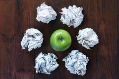 Grönt äpple och skrynkliga rester av papper Arkivbild