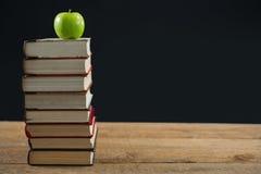 Grönt äpple på bokbunt Arkivfoton