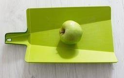 Grönt äpple på en skärbräda Fotografering för Bildbyråer