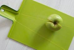 Grönt äpple på en skärbräda Arkivfoton