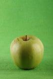 Grönt äpple på grön bakgrund Arkivbilder