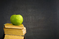 Grönt äpple på lärobok Arkivbilder