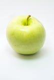 Grönt äpple på vit yttersida Arkivbild