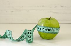 Grönt äpple som slås in i cm på vit träbakgrundsintelligens Arkivbilder