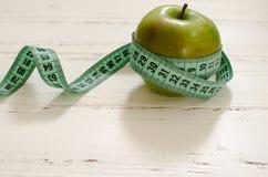 Grönt äpple som slås in i cm på vit träbakgrundsintelligens Royaltyfri Foto