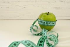 Grönt äpple som slås in i cm på vit träbakgrundsintelligens Royaltyfri Fotografi