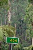 Grönt baner för tecken 404 i en djup skog Arkivfoto