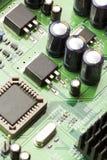 Grönt bräde för elektrisk strömkrets med mikrochipers och transistorer Arkivfoton