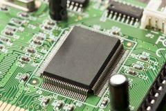 Grönt bräde för elektrisk strömkrets med mikrochipers och transistorer Arkivbild