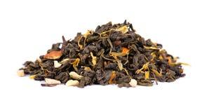 Grönt Ceylon te med torra blommor och kanderade apelsinen som isoleras på vit bakgrund close upp arkivbild