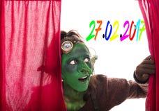 Grönt elakt troll som öppnar en röd gardin, datum av rosen måndag Royaltyfria Bilder