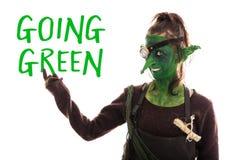 Grönt elakt troll som pekas av gående gräsplan för text, hållbara developmen Arkivfoto