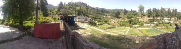 Grönt fält och litet byar och byfolk royaltyfria bilder