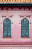 Grönt fönster för tappning på den gammala rosa väggen Arkivfoto