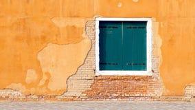 Grönt fönster på guling och byggnad för tegelstenvägg royaltyfri bild