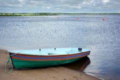 Grönt fartyg med band på kusten bak vatten Royaltyfria Foton