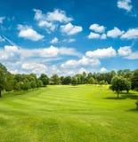 Grönt golffält och blå molnig himmel arkivbilder