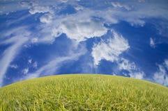 Grönt gräs för härligt landskap och dramatisk blå himmel Royaltyfri Bild