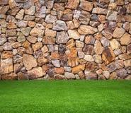 Grönt gräs med brun stenbakgrund royaltyfria foton