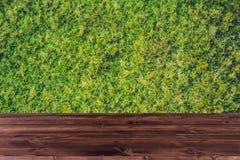 Grönt gräs med det wood tabellskrivbordet arkivbilder