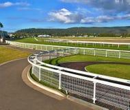 Grönt gräs och vita staket av en australisk gräshäst för land Arkivfoto