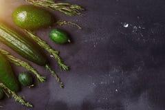 Grönt grönsak-, frukt- och örtsortiment på svart bakgrund Bästa sikt för kopieringsutrymme Rosmarin spiskummin, gurkor, avokado,  royaltyfri bild