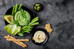 Grönt grönsakmellanmålbräde med olika dopp Hummus, örthummus eller pesto med smällare, grissinibröd, nya grönsaker arkivbild