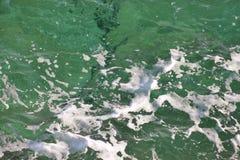 Grönt havsvatten för turkos med havsskum som bakgrund, slut upp Yttersida av havet med vågor, färgstänk, skum och bubblor royaltyfria bilder