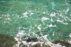 Grönt havsvatten för turkos med havsskum som bakgrund, slut upp Yttersida av havet med vågor, färgstänk, skum och bubblor arkivfoto
