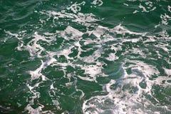Grönt havsvatten för turkos med havsskum som bakgrund, slut upp Yttersida av havet med vågor, färgstänk, skum och bubblor royaltyfri foto