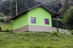 Grönt hus på berget arkivfoton
