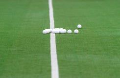 Grönt konstgjort gräshockeyfält med linjer och bollar arkivbild